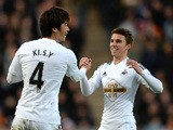 Ki Sung-Yueng of Swansea City celebrates scoring the opening goal with team-mate Tom Carroll during the Barclays Premier League match between Hull City and Swansea City at KC Stadium on December 20, 2014