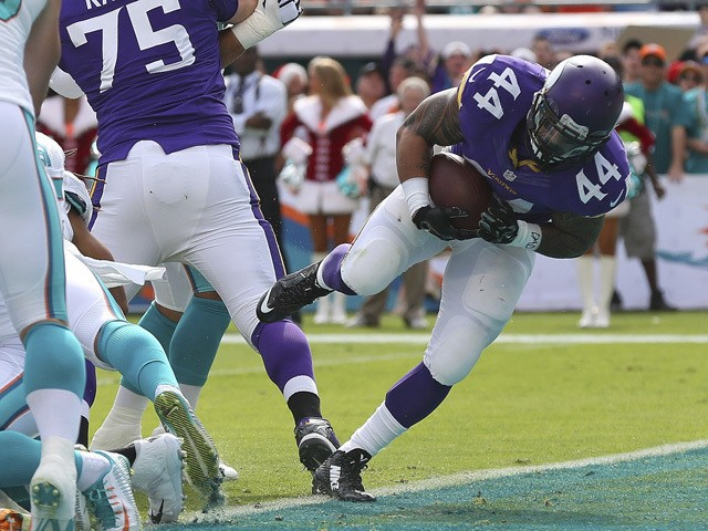 Running back Matt Asiata #44 of the Minnesota Vikings scores a first quarter touchdown against the Miami Dolphins during a game at Sun Life Stadium on December 21, 2014
