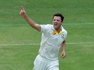 Josh Hazlewood of Australia celebrates taking the wicket of Cheteshwar Pujara of India during day four of the 2nd Test match between Australia and India at The Gabba on December 20, 2014
