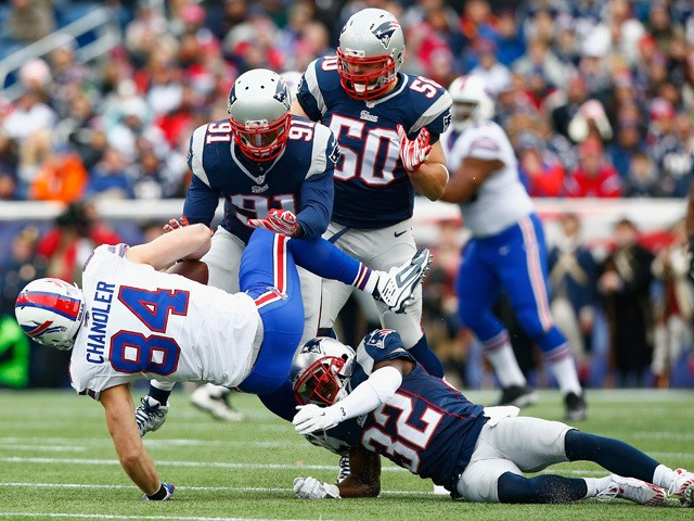 Scott Chandler #84 of the Buffalo Bills is tackled after catching a pass during the first quarter against the New England Patriots at Gillette Stadium on December 28, 2014