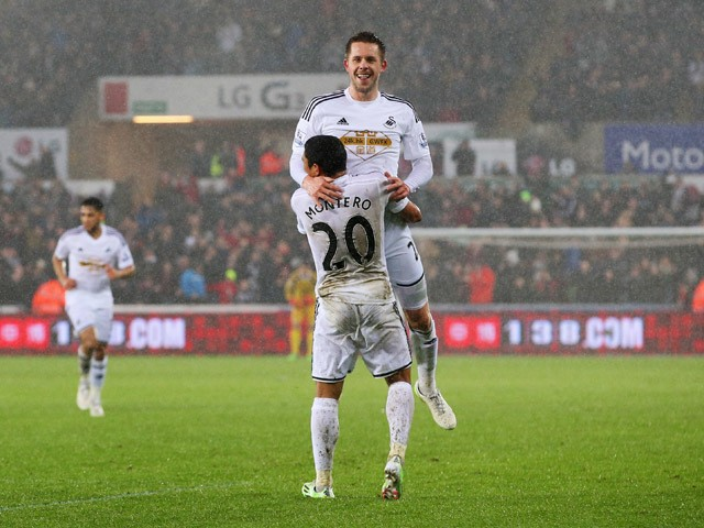 Gylfi Sigurdsson of Swansea City celebrates with Jefferson Montero as he scores their first goal during the Barclays Premier League match between Swansea City and Aston Villa at Liberty Stadium on December 26, 2014