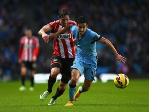Jesus Navas of Manchester City is challenged by Billy Jones of Sunderland during the Barclays Premier League match between Manchester City and Sunderland at Etihad Stadium on January 1, 2015