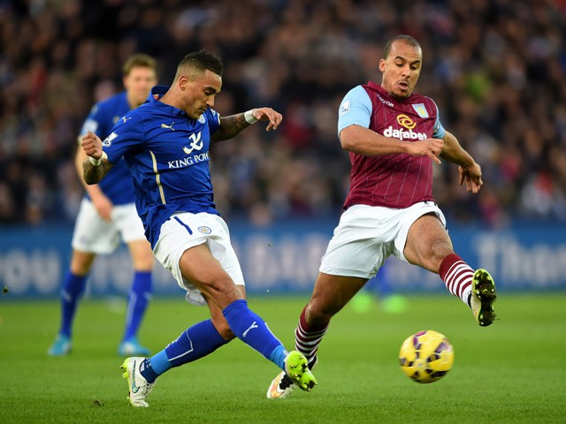 Danny Simpson of Leicester City passes the ball as Gabriel Agbonlahor of Aston Villa closes in during the Barclays Premier League match between Leicester City and Aston Villa at The King Power Stadium on January 10, 2015
