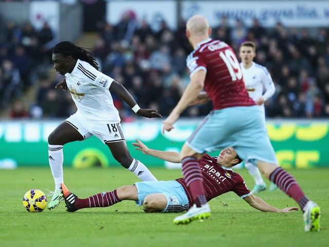 Bafetibis Gomis of Swansea City is tackled by Mark Noble of West Ham United during the Barclays Premier League match between Swansea City and West Ham United at Liberty Stadium on January 10, 2015