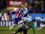 Atletico Madrid's French forward Antoine Griezmann jumps over Rayo Vallecano's goalkeeper Tono Rodriguez after scoring during the Spanish League football match Atletico de Madrid vs Rayo Vallecano at Vicente Calderon stadium in Madrid on January 24, 2015
