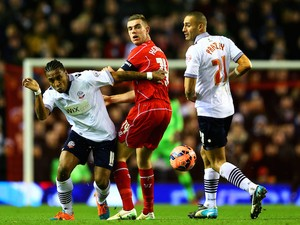 Jordan Henderson of Liverpool battles for the ball with Neil Danns and Darren Pratley of Bolton Wanderers during the FA Cup Fourth Round match on January 24, 2015