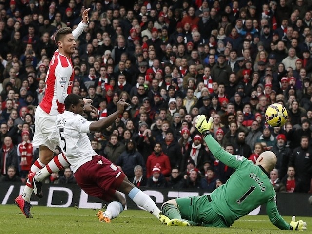 Arsenal's French striker Olivier Giroud (L) lifts the ball over Aston Villa's US goalkeeper Brad Guzan (R) to score the opening goal during the English Premier League football match on February 1, 2015