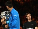 Andy Murray of Great Britain looks on as Novak Djokovic of Serbia holds the Norman Brookes Challenge Cup after he won the Australian Open on February 1, 2015