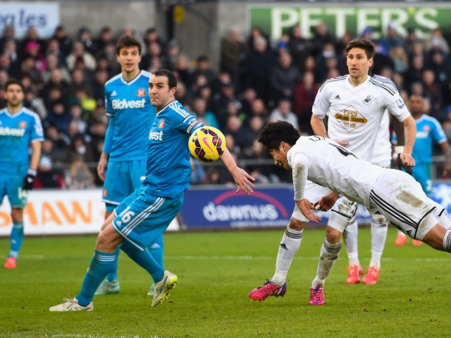 Swansea City player Ki Sung-Yueng dives to head the first Swansea goal during the Barclays Premier League match between Swansea City and Sunderland at Liberty Stadium on February 7, 2015