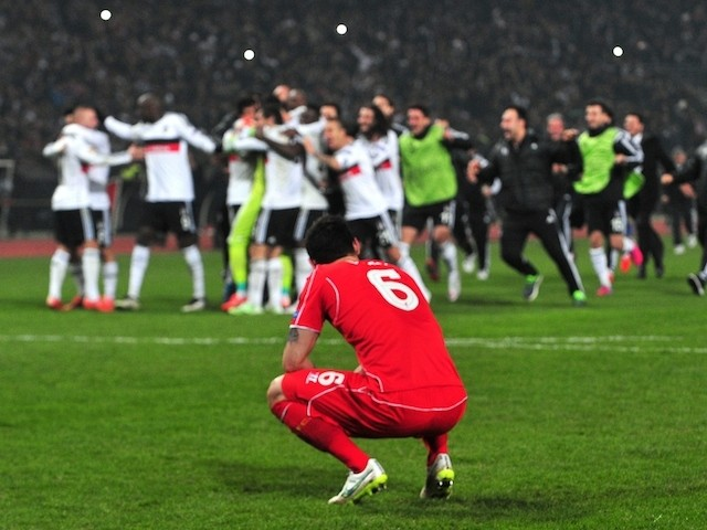 Liverpool's Dejan Lovren reacts after missing the last penalty while Besiktas' players celebrate during the UEFA Europa League round of 32 second-leg football match Besiktas  on February 26, 2015