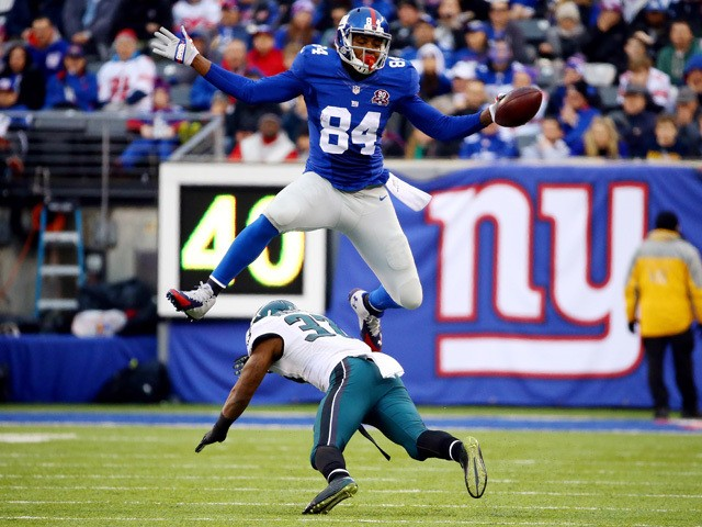 Larry Donnell #84 of the New York Giants jumps over Jaylen Watkins #37 of the Philadelphia Eagles in the third quarter during a game at MetLife Stadium on December 28, 2014