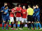 Angel di Maria of Manchester United remonstrates with referee Michael Oliver as he receives the yellow card dur