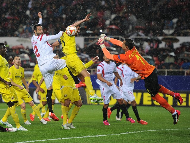 Sergio Asenjo of Villarreal fists the ball away from Vicente Iborra of FC Sevilla during the UEFA Europa League Round of 16, Second Leg match between FC Sevilla and Villarreal CF at Estadio Ramon Sanchez Pizjuan on March 19, 2015