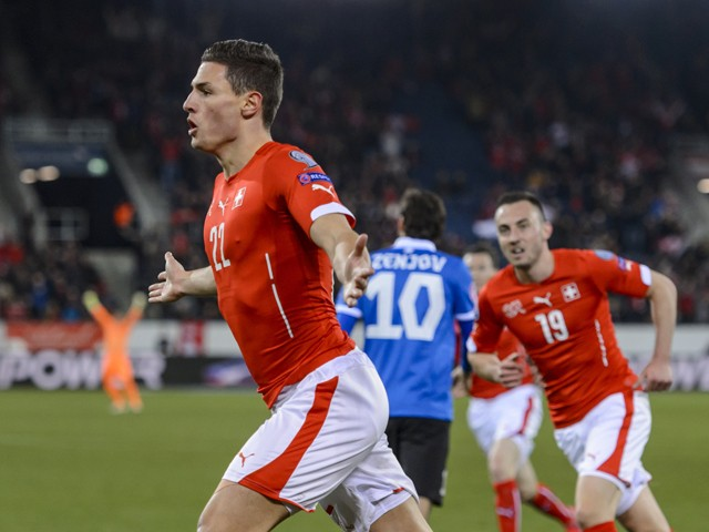 Switzerland's defender Fabian Schaer celebrates with teammate forward Josip Drmic after he scored the first goal during the Euro 2016 qualifying football match between Switzerland and Estonia at the Swissporarena stadium in Lucerne on March 27, 2015