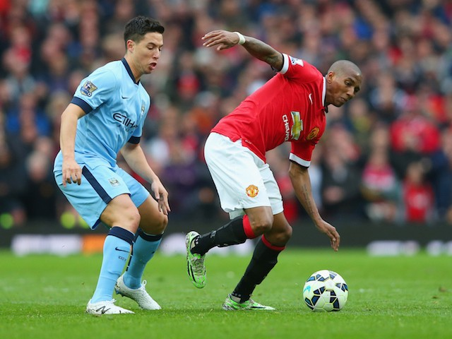 Ashley Young of Manchester United evades Samir Nasri of Manchester City during the Barclays Premier League match between Manchester United and Manchester City at Old Trafford on April 12, 2015