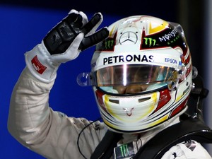 Mercedes AMG Petronas British driver Lewis Hamilton flashes the sign for victory after winning the pole position for the Formula One Bahrain Grand Prix following the qualification session at the Sakhir circuit in the desert south of the Bahraini capital,