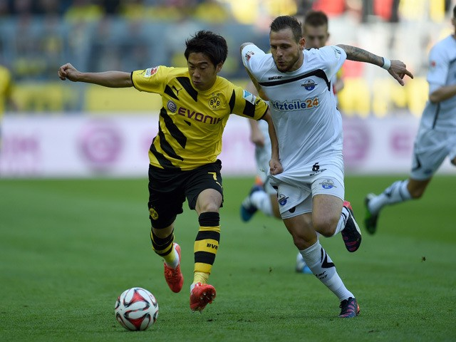 Dortmund's Japanese midfielder Shinji Kagawa and Paderborn's midfielder Marvin Bakalorz vie for the ball during the German first division Bundesliga football match Borussia Dortmund vs SC Paderborn in Dortmund, western Germany, on April 18, 2015