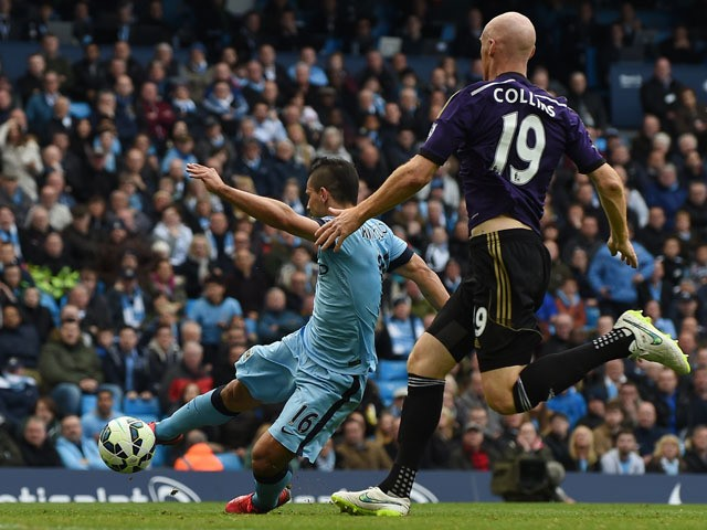 Manchester City's Argentinian striker Sergio Aguero (L) scores their second goal during the English Premier League football match between Manchester City and West Ham United at the Etihad Stadium in Manchester, north west England on April 19, 2015