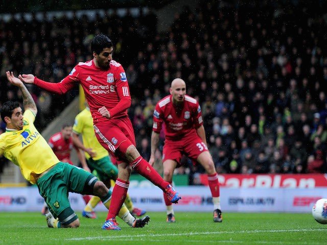 Luis Suarez of Liverpool takes a shot on goal as Bradley Johnson of Norwich slides in during the Barclays Premier League match between Norwich City and Liverpool at Carrow Road on April 28, 2012