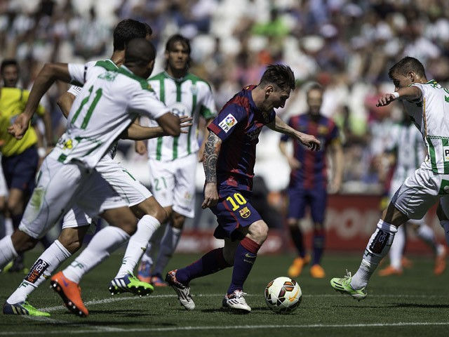 Lionel Messi of FC Barcelona competes for the ball with Aleksandar Pantic of Cordoba CF during the La Liga match between Cordoba CF and Barcelona FC at El Arcangel stadium on May 2, 2015