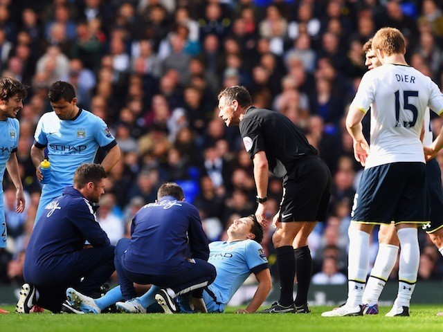 An injured Samir Nasri of Manchester City is given assistance as referee Andre Marriner looks on during the Barclays Premier League match between Tottenham Hotspur and Manchester City at White Hart Lane on May 3, 2015