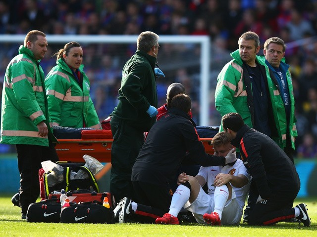 Luke Shaw of Manchester United receives treatment before leaving the field on a stretcher during the Barclays Premier League match between Crystal Palace and Manchester United at Selhurst Park on May 9, 2015