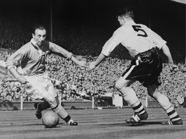 Blackpool's forward Stanley Matthews dribbles past Bolton's midfielder Barass during the English Cup final 03 May 1953