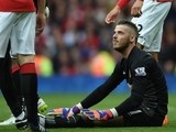 Manchester United's Spanish goalkeeper David de Gea lies on the ground after being injured during the English Premier League football match between Manchester United and Arsenal at Old Trafford in Manchester, northwest England, on May 17, 2015