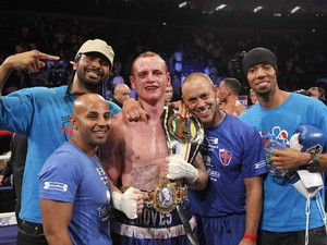 George Groves (C) celebrates with David Haye (L) after winning his fight against James DeGale, during their British and Commonwealth Super-Middleweight Championship title boxing fight at the O2 Arena, in London on May 21, 2011