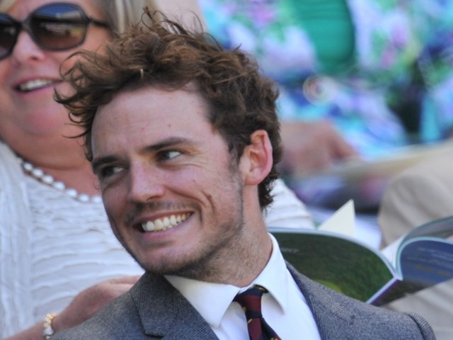 Sam Claflin and Laura Haddock sit in the royal box on Centre Court as they wait for the start of the women's singles semi-final matches on day ten of the 2014 Wimbledon Championships at The All England Tennis Club in Wimbledon, southwest London, on July 3