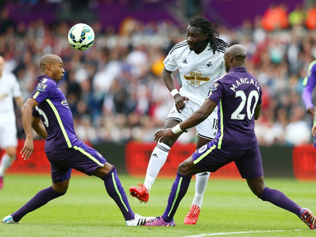 Bafetibis Gomis of Swansea City is closed down by Fernandinho of Manchester City and Eliaquim Mangala of Manchester City during the Barclays Premier League match between Swansea and Manchester City at the Liberty Stadium on May 17, 2015