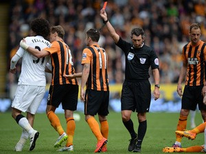 Referee Lee Probert shows a red card to Manchester United's Belgian midfielder Marouane Fellaini after a foul on Hull City's Irish defender Paul McShane during the English Premier League football match between Hull City and Manchester United at the KC Sta