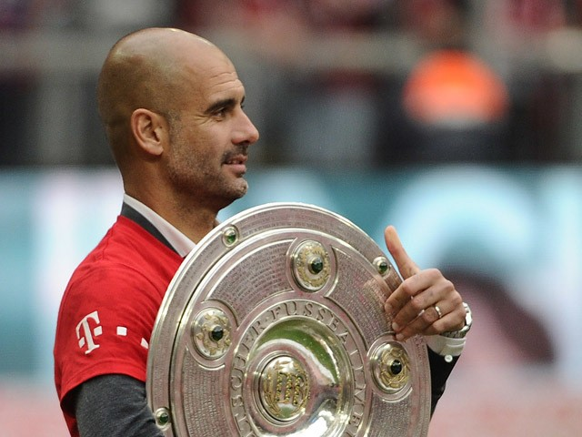 Bayern Munich's Spanish head coach Pep Guardiola holds the trophy as his team celebrates wining their 25th Bundesliga title after German first division Bundesliga football match FC Bayern Munich vs 1 FSV Mainz 05 at the Allianz Arena in Munich, southern G