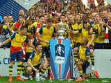 The Arsenal team pose with the trophy after winni