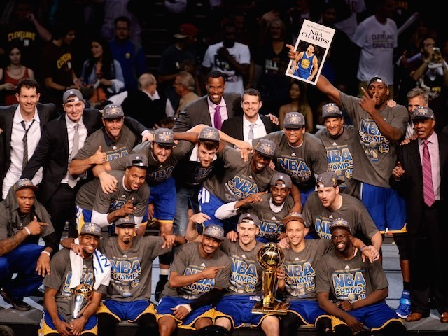 The Golden State Warriors celebrate with the Larry O'Brien trophy after winning the NBA title on June 16, 2015