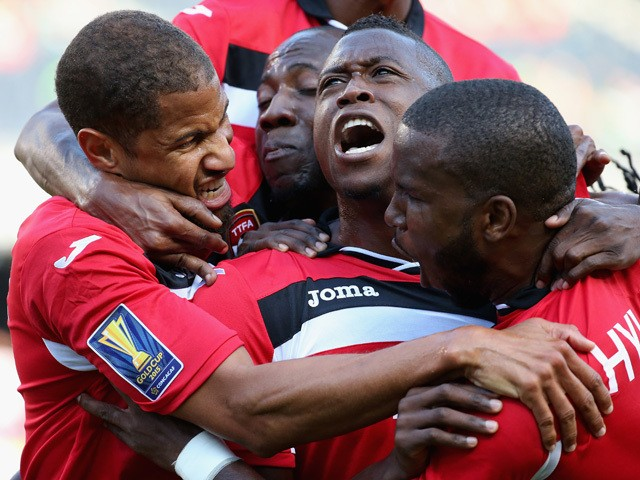 Sheldon Bateau #4 of Trinidad & Tobago (Center) celebrates a first half goal against Guatemala with teammates including Radanfah Abu Bakr #6 (L) and Khaleem Hyland #8 (R) during a match in the 2015 CONCACAF Gold Cup at Soldier Field on July 9, 2015