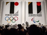 People wave flags as the new Olympic emblems are unveiled during a ceremony for the Tokyo 2020 Olympic and Paralympic Games at the Tokyo Metropolitan Government Plaza on July 24, 2015