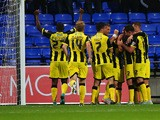 Goalkeeper Ben Amos of Bolton Wanderers looks dejected as Matt Palmer of Burton Albion (obscured) celebrates with team mates as he scores their first goal during the Capital One Cup first round match between Bolton Wanderers and Burton Albion at Macron St