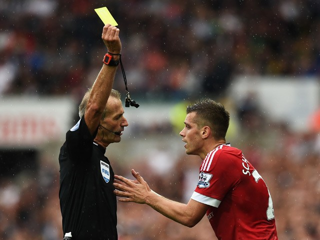 Referee Martin Atkinson shows the yellow card to Morgan Schneiderlin of Manchester United during the Barclays Premier League match between Swansea City and Manchester United at Liberty Stadium on August 30, 2015