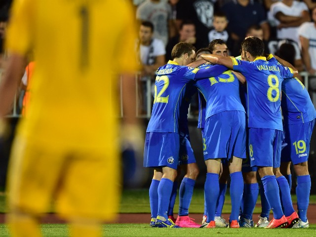 Bate Borisov's midfielder Igor Stasevich (hidden) and his team mates celebrate after scoring a goal during the UEFA Champions League playoff football match between FK Partizan and FC BATE Borisov at FK Partizan stadium in Belgrade on August 26, 2015.