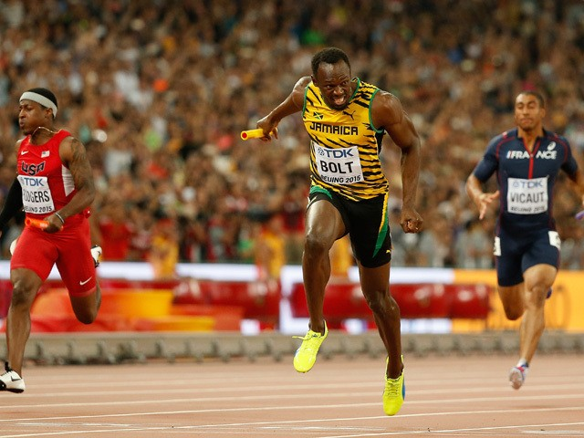 Usain Bolt of Jamaica crosses the finish line to win gold in the Men's 4x100 Metres Relay final ahead of Mike Rodgers of the United States during day eight of the 15th IAAF World Athletics Championships Beijing 2015 at Beijing National Stadium on August 2