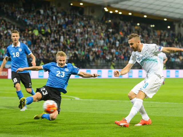 Jasmin Kurtic (R) of Slovenia vies with Estonia's Taijo Teniste (C) during the Euro 2016 qualifying football match between Slovenia and Estonia at the Ljudski Vrt stadium in Maribor, Slovenia on September 8, 2015