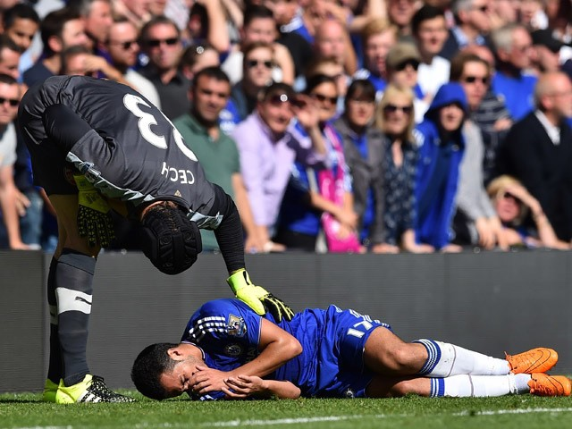 Arsenal's Czech goalkeeper Petr Cech (L) attends to injured Chelsea's Spanish midfielder, Pedro during the English Premier League football match between Chelsea and Arsenal at Stamford Bridge in London on September 19, 2015