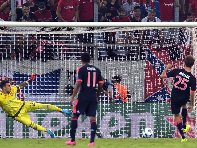 Bayern Munich's German forward Thomas Muller scores against Olympiakos during their UEFA Champions League football match, Group F, between Olympiakos and Bayern Munich at the Karaiskaki stadium in Piraeus, near Athens on September 16, 2015