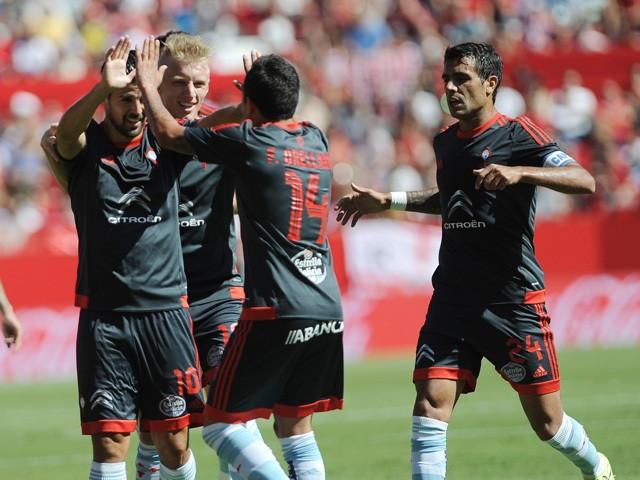 Celta Vigo's forward Nolito (L) celebrates a goal with teammates during the Spanish league football match Sevilla FC vs Celta de Vigo at the Ramon Sanchez Pizjuan stadium in Sevilla on September 20, 2015