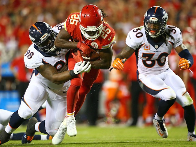 Jamaal Charles #25 of the Kansas City Chiefs is tackled by Darius Kilgo #98 of the Denver Broncos during the game at Arrowhead Stadium on September 17, 2015 in Kansas City, Missouri.