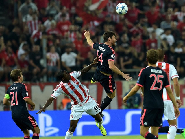 Bayern Munich's Spanish midfielder Xabi Alonso fights for the ball with Olympiakos Nigerian forward Ideye Brown during a Group F, UEFA Champions League football match between Olympiacos and Bayern Munich at the Karaiskaki stadium in Piraeus, near Athens o