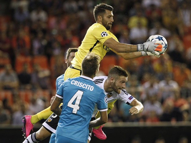 Zenit's goalkeeper Yury Lodygin (top) vies with Valencia's German defender Shkodran Mustafi (R) during the UEFA Champions League group H football match Valencia CF vs FC Zenit at the Mestalla stadium in Valencia on September 16, 2015