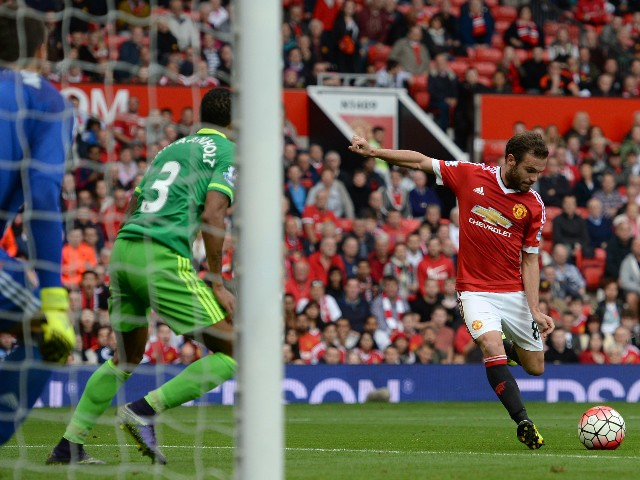 Manchester United's Spanish midfielder Juan Mata (R) shoots the score their third goal past Sunderland's Romanian goalkeeper Costel Pantilimon (L) during the English Premier League football match between Manchester United and Sunderland at Old Trafford in
