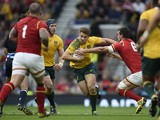 Australia's wing Drew Mitchell (C) runs past Wales' flanker and captain Sam Warburton (R) during a Pool A match of the 2015 Rugby World Cup between Wales and Australia at Twickenham Stadium, south west London, on October 10, 2015